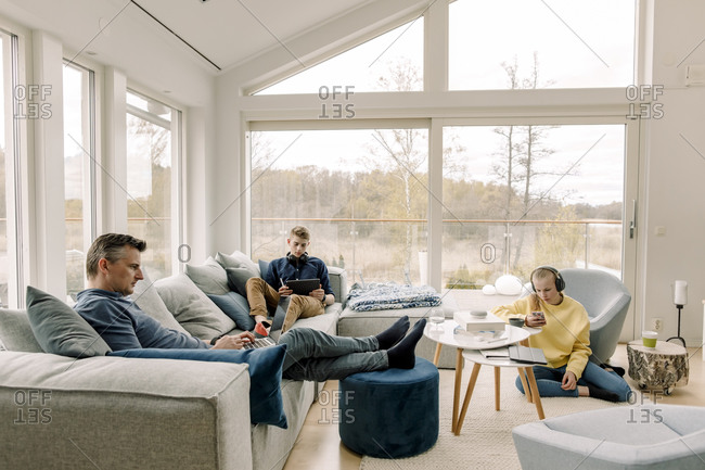 Father and children using wireless technology at home