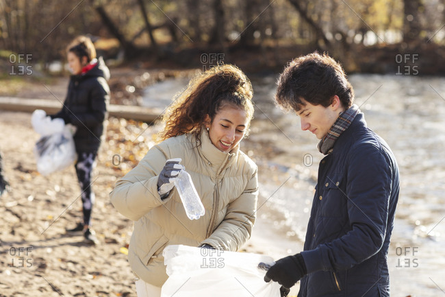 Smiling female volunteer with male friend holding plastic bottle in garbage bag