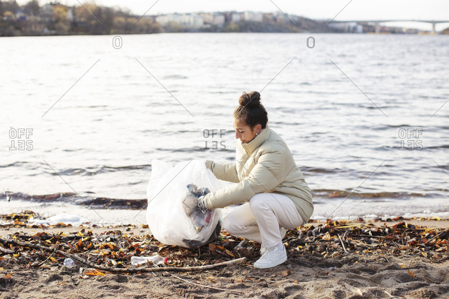 Young female environmentalist collecting waste while crouching by lake