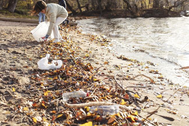 Female volunteer collecting plastic garbage by lake
