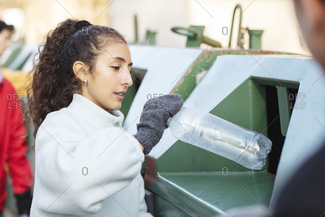 Smiling female environmentalist with friend throwing plastic bottle in garbage can