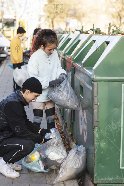 Young male and female environmentalists throwing recycling waste in garbage can