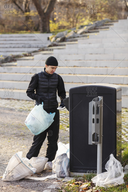 Male environmentalist with plastic waste standing by garbage can