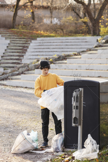 Male volunteer with plastic waste standing by garbage can