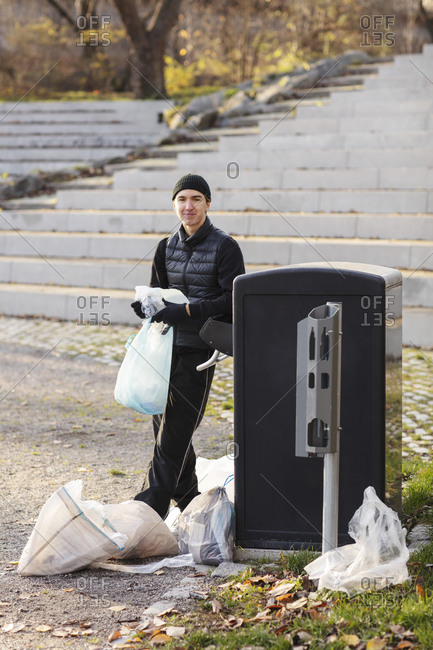 Portrait of environmentalist with plastic waste standing by garbage can