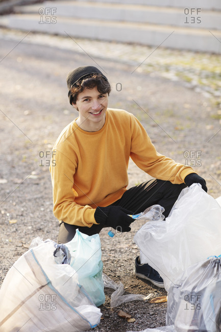 Portrait of smiling male volunteer with plastic waste kneeling on ground