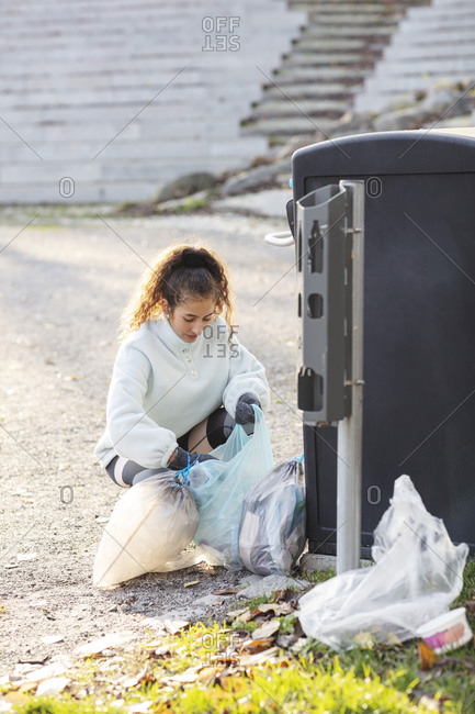 Female volunteer crouching with plastic waste by garbage can