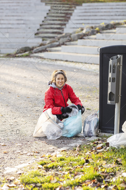 Portrait of female volunteer crouching with plastic waste by garbage can