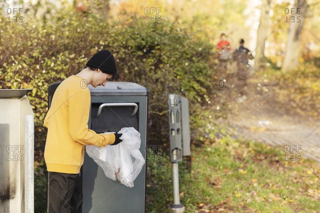 Male volunteer throwing plastic waste in garbage can