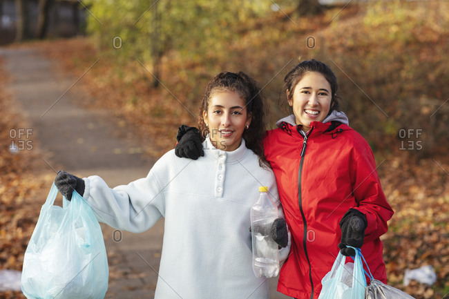 Portrait of female environmentalists holding plastic waste in park