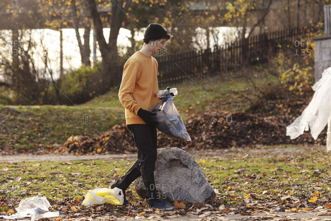 Male volunteer collecting garbage while walking in park
