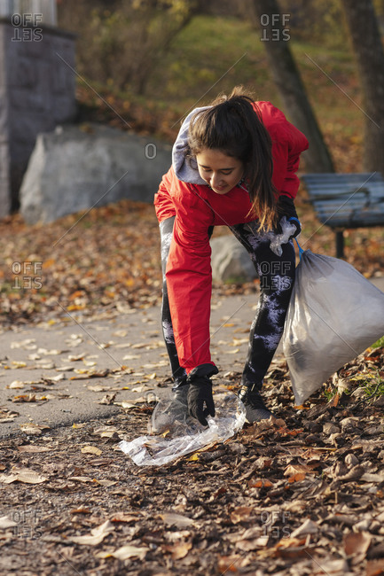 Smiling female environmentalist collecting plastic waste in park during autumn