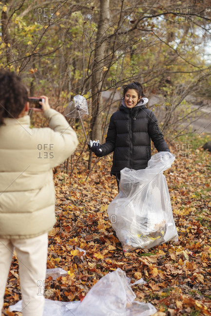 Young female environmentalist photographing smiling teenager holding microplastics in park