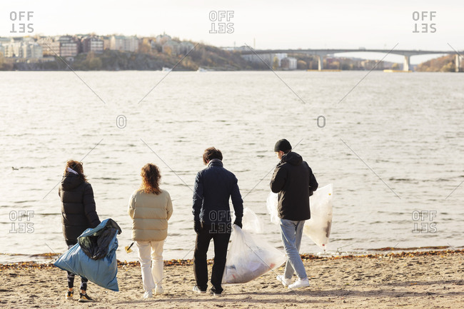 Rear view of environmentalists with microplastics garbage walking against lake