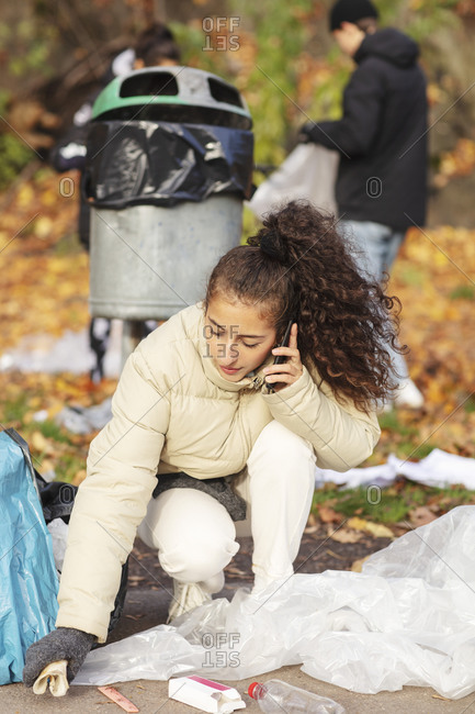 Young female volunteer talking on smart phone while collecting garbage in park