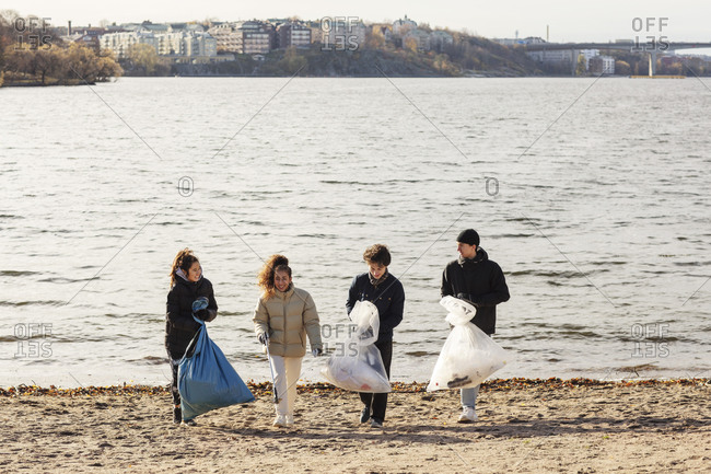 Young male and female environmentalists with collected microplastics walking against lake
