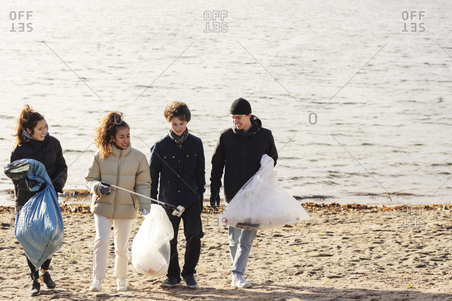 Male and female environmentalists with microplastics garbage walking against lake