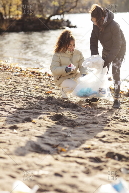 Young female environmentalist with teenage girl collecting waste while crouching on land