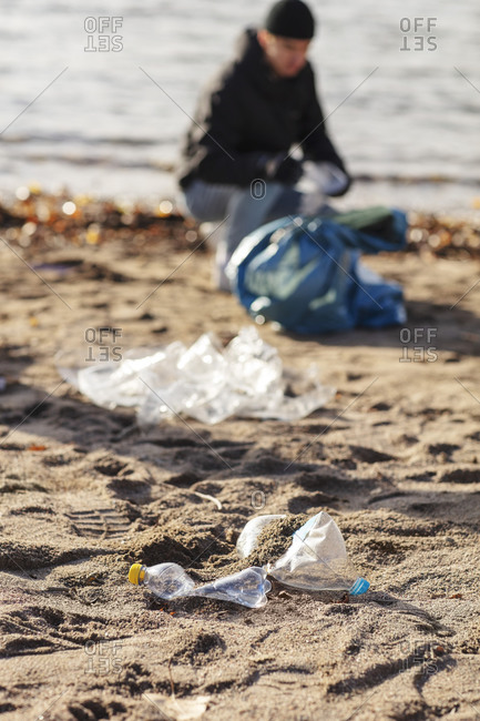 Young environmentalist collecting plastic waste by lake