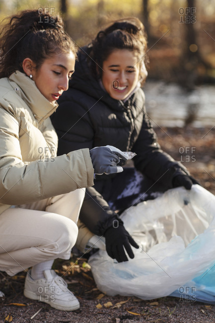Young female environmentalist with smiling teenager holding microplastics while crouching on land