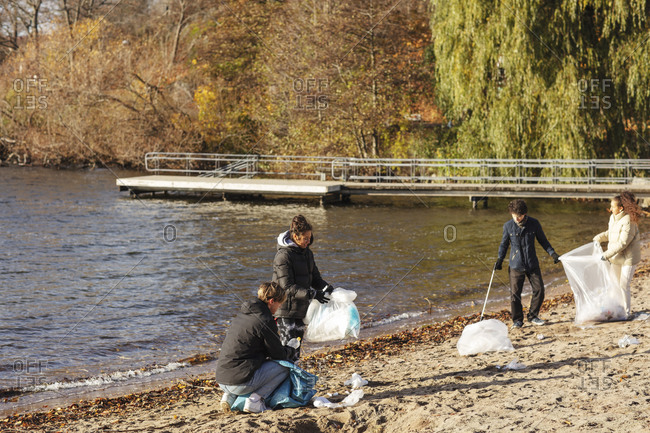 Male and female friends collecting plastic garbage by lake