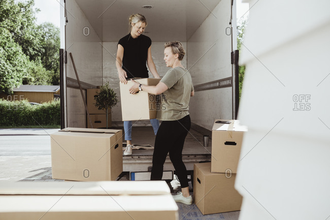 Women unloading boxes from moving van