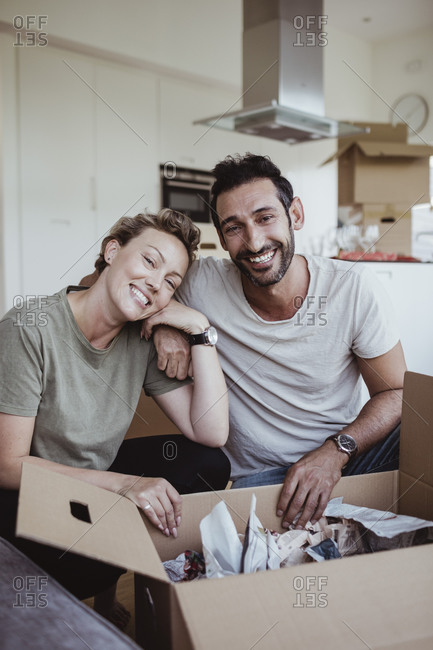 Portrait of smiling male and female partners unpacking cardboard boxes in new house