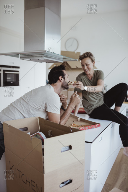 Smiling woman feeding pizza to male partner while sitting on kitchen counter in new house