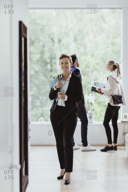 Portrait of smiling real estate agent while couple standing by window in new house