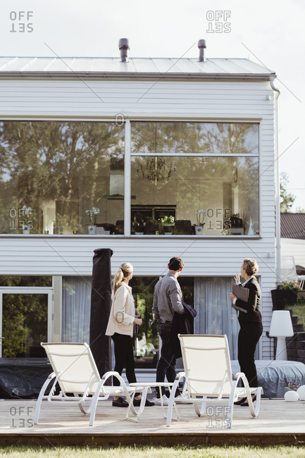 Side view of real estate agent showing new property to couple