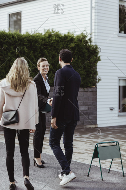 Smiling real estate professional greeting couple outside new house