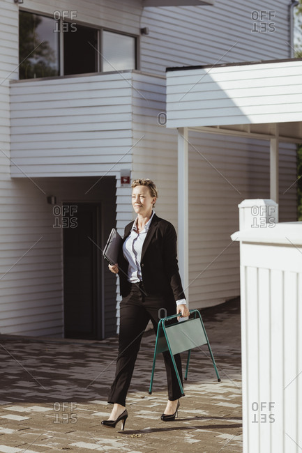 Smiling female real estate agent looking away while walking against house