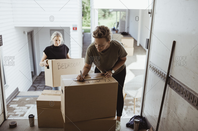 Woman holding box while female writing on cardboard box in moving van