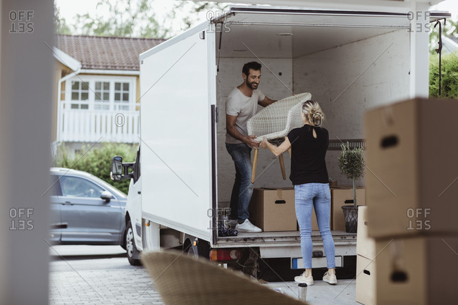 Smiling male and female partners unloading chair from van