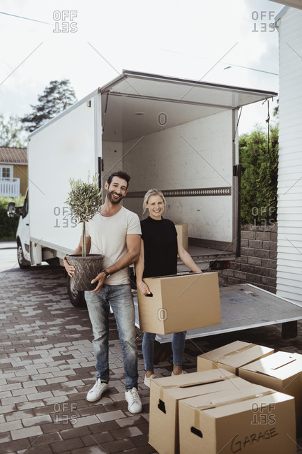 Portrait of smiling male and female partners unloading cardboard boxes during relocation
