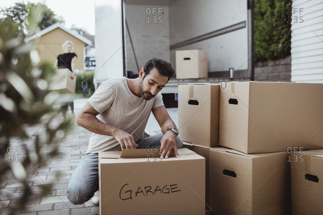 Man crouching by cardboard box while partner unloading luggage from moving van