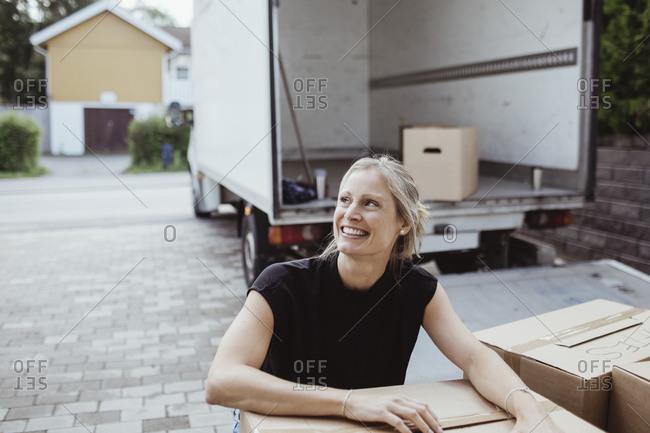 Smiling female by cardboard box looking away outside van