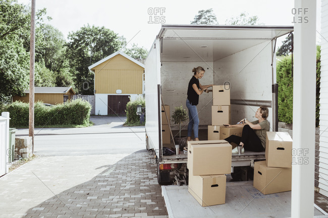 Side view of woman with boxes talking to female friend in moving van