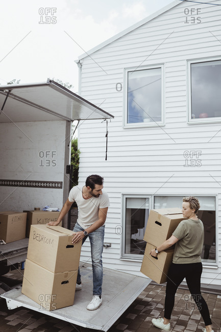 Male and female partners unloading cardboard boxes during relocation