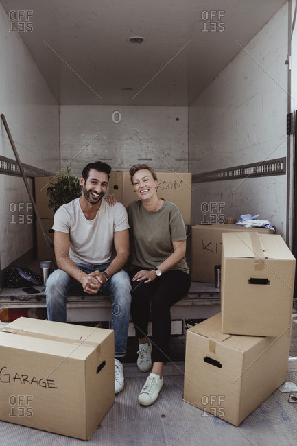 Portrait of smiling male and female partners sitting by cardboard boxes in van