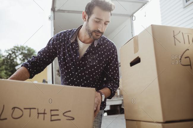 Man unloading cardboard boxes outside van