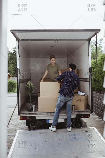 Smiling male and female friends unloading cardboard boxes during relocation