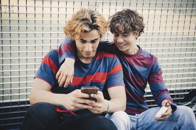 Smiling friends using smart phone while sitting against net in city