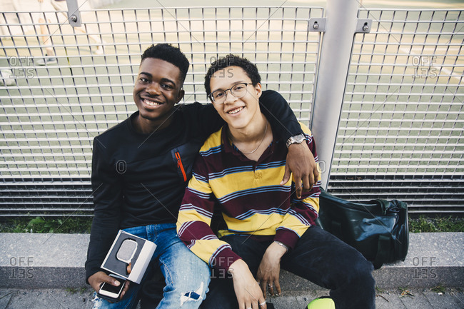 Portrait of smiling young men sitting against net