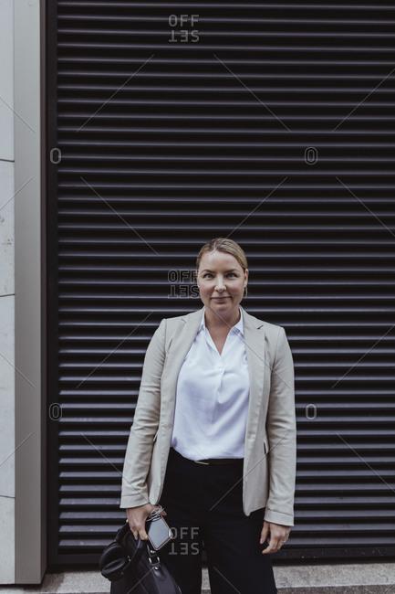 Portrait of entrepreneur with bag standing against shutter in city