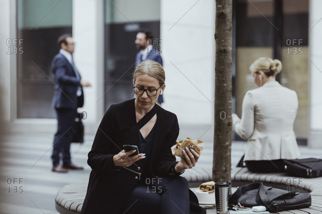 Entrepreneur with sandwich using smart phone while sitting in city