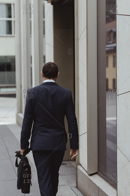 Rear view of businessman with bag walking by building in city