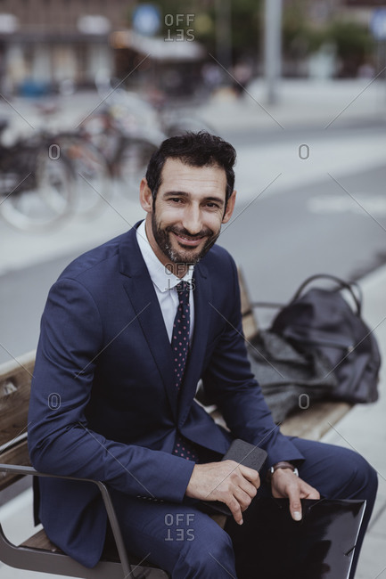 Portrait of smiling entrepreneur with smart phone and file sitting on bench in city