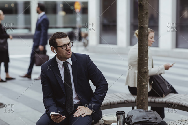 Entrepreneur with smart phone talking through in-ear headphones while sitting in city