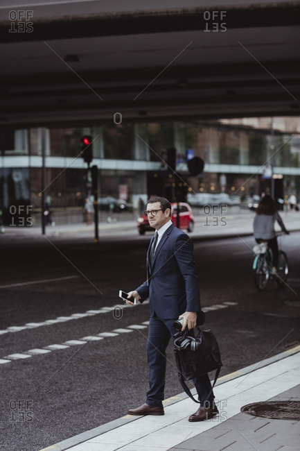 Businessman with bag and smart phone in city